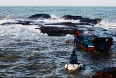 Un pescador en ondas Foto de archivo libre de regalías