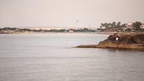 Un pescador está pescando en el mar en el amanecer, pescador de A en la roca contra el cielo del amanecer, siluetas de pescadores almacen de metraje de vídeo