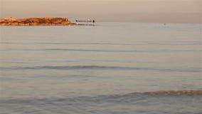 Un pescador está pescando en el mar en el amanecer, pescador de A en la roca contra el cielo del amanecer, siluetas de pescadores metrajes