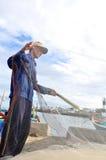 Un pescador está quitando las anchoas pesca de su red de pesca para comenzar un nuevo día laborable en la isla del hijo de LY Fotos de archivo libres de regalías