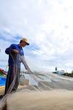 Un pescador está quitando las anchoas pesca de su red de pesca para comenzar un nuevo día laborable en la isla del hijo de LY Fotografía de archivo