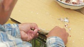 Un pescador mayor limpia un pequeño pescado Prepara un plato para la familia metrajes