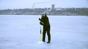 Un pescador perfora un agujero con un hielo perfora adentro invierno en la ciudad metrajes