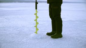 Un pescador perfora un agujero con un hielo perfora adentro invierno en un río congelado almacen de video