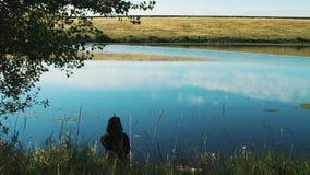 Un pescador se sienta en la orilla de una charca, un lago de un río Las cañas de pescar se lanzan en el agua y esperar almacen de video