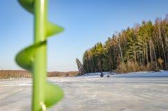 Un pescador solitario en el hielo del río fotos de archivo libres de regalías