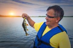Un pescador sostiene una captura foto de archivo