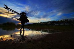 Un pescador va a la pesca en la puesta del sol Imagenes de archivo