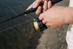 Un pescatore con una canna da pesca sulla sponda del fiume fotografie stock