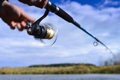 Un pescatore pesca un pesce Primo piano di filatura della bobina blurry fotografia stock libera da diritti