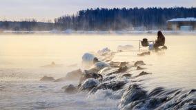 Un pescatore solo sul lago nebbioso con una canna da pesca, primo mattino, inverno Immagini Stock Libere da Diritti