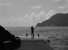 Un pescatore solo sulla costa italiana Fotografia Stock