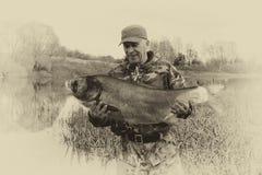 Un pescatore tiene un grande pesce fotografia stock libera da diritti