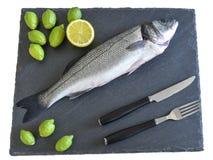 Un pesce crudo pronto da cucinare con la forcella, il coltello ed il limone sulla pietra s Immagini Stock Libere da Diritti