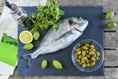 Un pesce crudo pronto da cucinare dell'orata con il limone e le olive sulla pietra Immagini Stock
