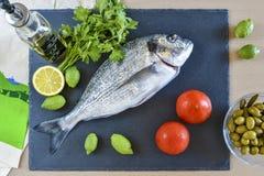 Un pesce crudo pronto da cucinare dell'orata con il limone e le olive sulla pietra Immagine Stock