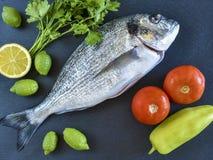 Un pesce crudo pronto da cucinare dell'orata con le verdure sull'ardesia di pietra Fotografia Stock
