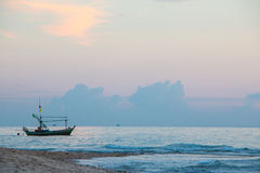 Un peschereccio con alba della spiaggia del mare Fotografie Stock