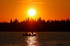 Un peschereccio profilato su un cielo arancio brillante Immagini Stock
