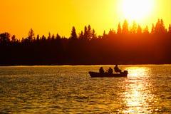 Un peschereccio profilato su un cielo arancio brillante immagini stock libere da diritti
