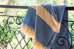 Un peshtemal turc blanc/serviette beiges et bleues sur des balustrades d'un fer travaillé avec la nature trouble à l'arrière-plan Images stock