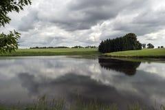 Un petit étang dans les bois avant la tempête photographie stock libre de droits