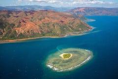Un petit îlot d'atoll avec le récif coralien en forme de coeur outre de la Côte Est de la grande île de Terre de la Nouvelle-Calé image libre de droits