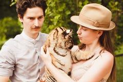 Un petit animal de tigre de prise d'homme et de femme Photo stock
