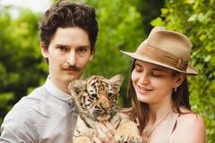 Un petit animal de tigre de prise d'homme et de femme Photographie stock