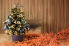 Un petit arbre de Noël sur un fond en bois pour des cartes postales et Photographie stock