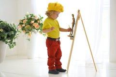 Un petit artiste dans les peintures jaunes de chapeau Photos stock