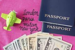 Un petit avion de jouet et des passeports bleus avec des dollars sur le tabl photographie stock