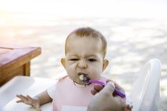Un petit bébé est fâché et ne veut pas manger avec une cuillère La fille infantile s'assied sur une chaise sur la plage au j image stock