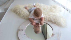 Un petit bébé nouveau-né mignon joue avec un miroir à la maison se trouvant sur le lit banque de vidéos