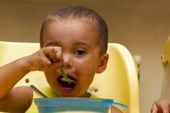 Un petit b mangeant son dîner et faisant un désordre photographie stock libre de droits