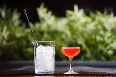 Un petit bas verre avec un cocktail alcoolique rouge est sur la table à côté d'un vase en verre complètement de grands morceaux c Photos libres de droits
