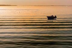 Un petit bateau d'isolement et a tiré comme silhouette sur une lagune calme de Venise Photographie stock