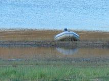 Un petit bateau de pêche a amarré sur un bord de barrages Photos libres de droits
