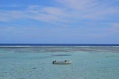 Un petit bateau de pêche en bois avec deux pêcheurs sur un seaview avec l'horizon qui sépare l'eau et le ciel Photos libres de droits