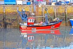 Un petit bateau de pêche rouge amarré dans le port photos libres de droits