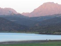 Un petit bateau de pêche sur un barrage avec des montagnes à l'arrière-plan Photos libres de droits