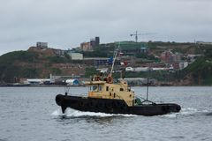 Un petit bateau de remorquage est sur l'eau calme photos stock