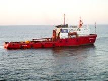 Un petit bateau de service dans un port industriel de cargaison Un bateau dans le s Photo stock
