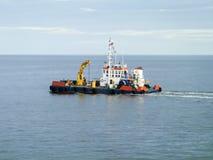 Un petit bateau de service dans un port industriel de cargaison Un bateau en mer Image libre de droits