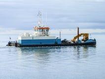 Un petit bateau de service dans un port industriel de cargaison Un bateau en mer Photographie stock libre de droits