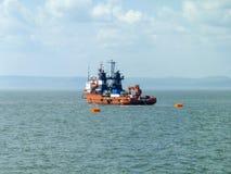Un petit bateau de service dans un port industriel de cargaison Un bateau en mer Photographie stock