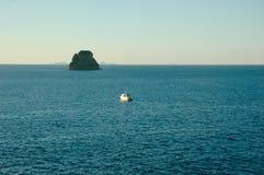 Un petit bateau est rapetissé par une grande roche se levant hors de l'océan Photographie stock
