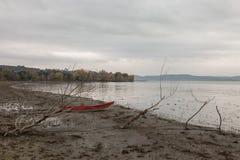 Un petit bateau rouge sur un rivage de lac près de quelques arbres squelettiques, un jour déprimé photographie stock libre de droits