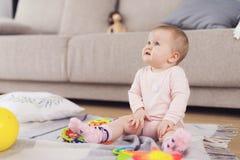 Un petit beau bébé s'assied sur le plancher et joue avec les jouets lumineux et fleuris photo stock