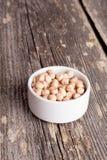 Un petit bol blanc de haricots organiques secs de pois chiche, vertical Photographie stock libre de droits